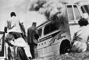 """14 May 1961, Anniston, Alabama, USA --- Passengers of this smoking Greyhound bus, some of the members of the """"Freedom Riders,"""" a group sponsored by the Congress of Racial Equality (CORE), sit on the ground after the bus was set afire 5/14, by a mob of Caucasians who followed the bus from the city.  The mob met the bus at the terminal, stoned it & slashed the tires, then followed the bus from town.  BPA2# 47. --- Image by © Bettmann/CORBIS"""
