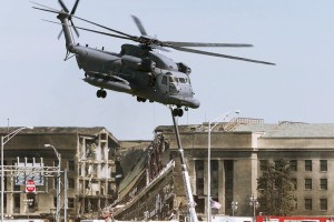 A military helicopter takes off near the damaged area of the Pentagon Building as fire fighters and rescue workers continue to battle smoke at the U.S. Military Headquarters outside of Washington, September 12, 2001. The Pentagon and the World Trade Center Buildings in New York City were attacked yesterday after terrorists hijacked commercial jetliners and crashed them into the buildings.