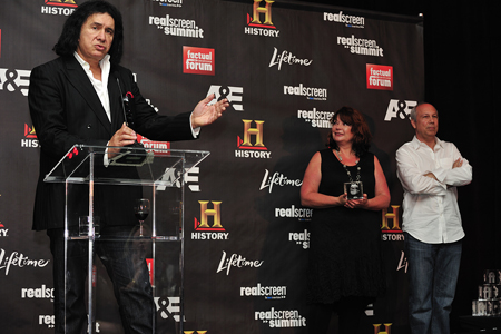 Gene Simmons is inducted into the Factual Entertainment Awards Hall Of Fame by Realscreen's Claire Macdonald (right) and A&E's Bob Debitetto (far right). (C) 2011. Photo: Rahoul Ghose