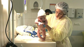 A nurse holds up a newborn baby.(photo credit: PERNEL)