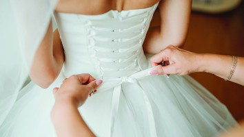 Bridesmaid makes bow-knot on the back of brides wedding dress