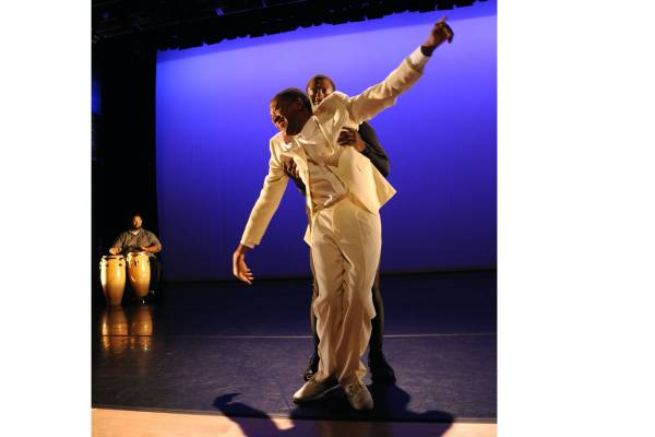 On a dramatically lit stage in a past, a Black man in a white suit stands front and center, his knees bent and his arms open. Right behind him, another Black man in a black suit holds him under his arms. In the background, a Black man sits at a pair of drums. The shot is taken from a 2016 Sins Invalid performance, a group whose executive and artistic director, Patty Berne, is a Disability Futures fellow.